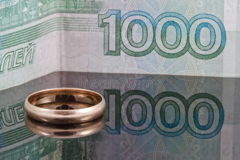 Golden wedding ring on the background of banknotes thousand rubles royalty free stock photos