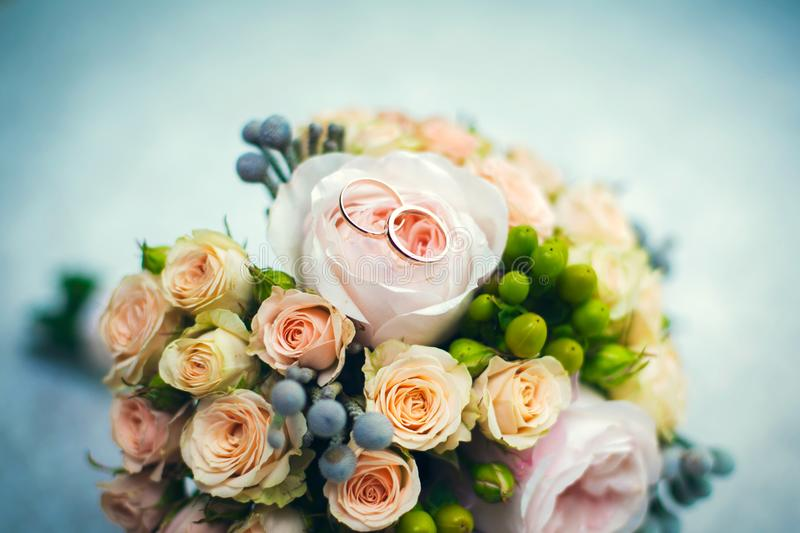 Golden wedding rings bouquet of roses close-up stock photography