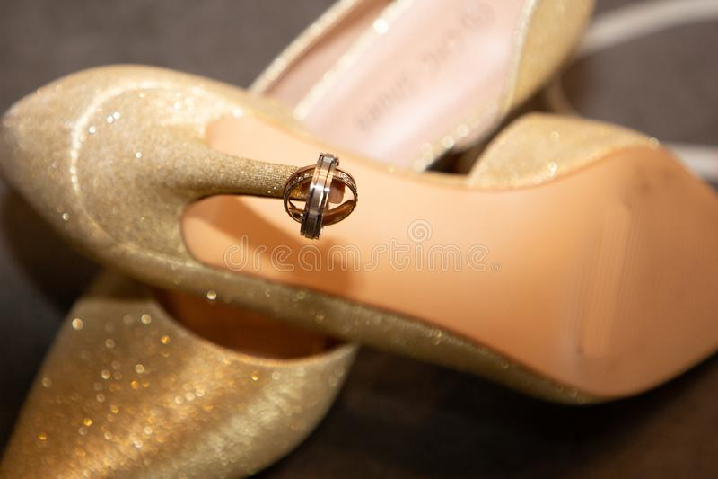 Golden wedding rings on bride shoes symbol of love and marriage royalty free stock image