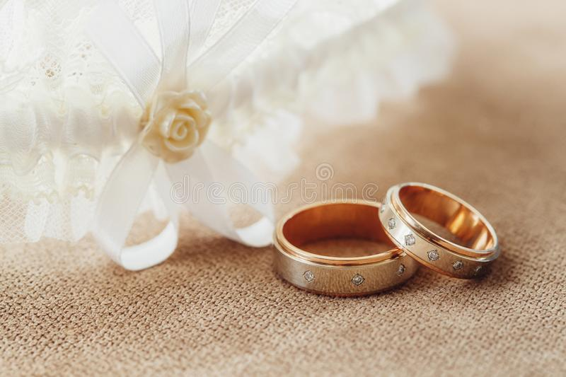 Golden wedding rings and garter of the bride, marriage concept. Golden rings and garter of the bride, wedding composition on sofa. Marriage concept royalty free stock photo