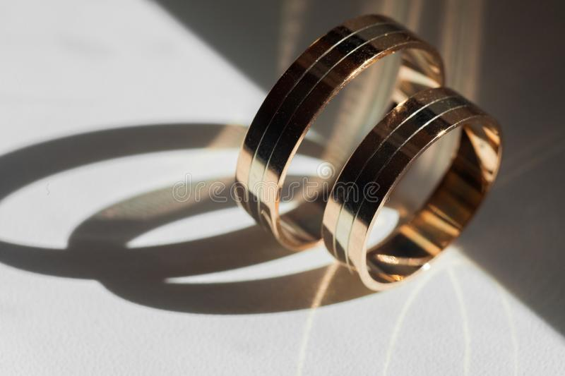 Golden wedding rings. For bride and groom standing on the es stock photos