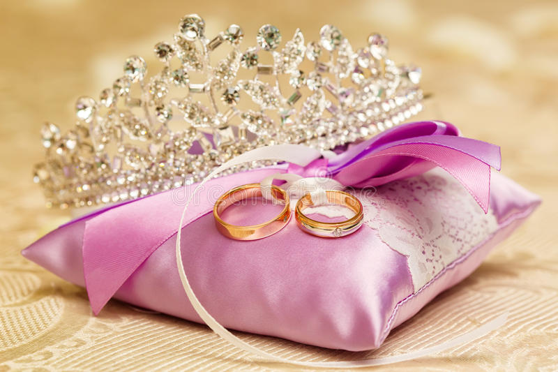 Golden wedding rings on the purple lace pillow. Marriage concept. Golden wedding rings on the purple lace pillow, closeup. Marriage concept royalty free stock photo