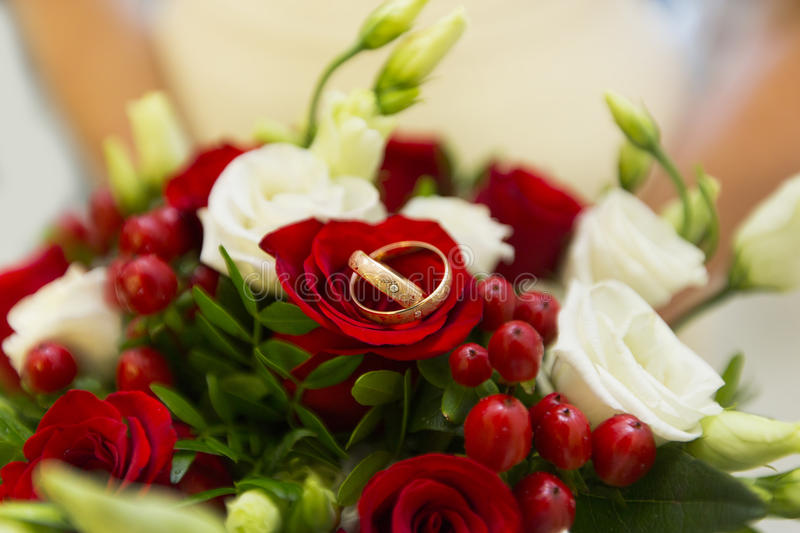 Golden wedding rings among red berries and white and red roses of wedding bouquet royalty free stock photography