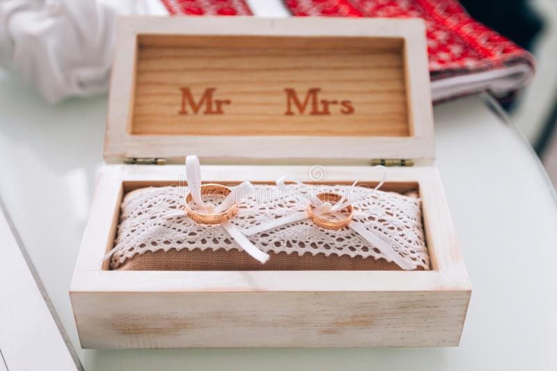 Golden wedding rings in a white wooden box. Wedding decoration. Symbol of family, unity and love.  royalty free stock photography