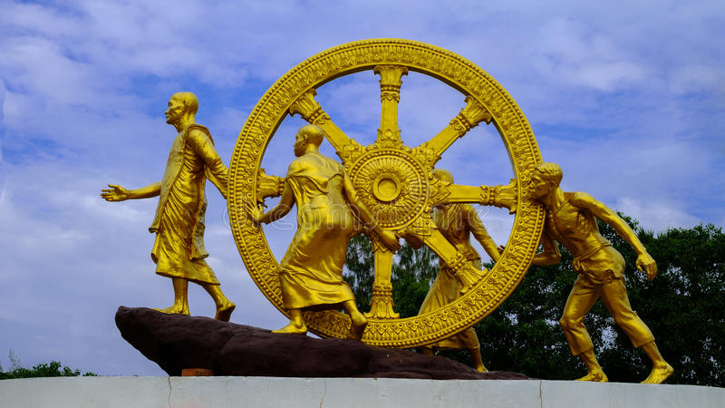 Golden Wheel of Dhamma on sky clouds. Dharmachakra Thai Art in public temple Wheel of Dhamma symbol of Buddhism royalty free stock photography