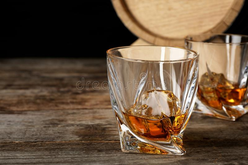 Golden whiskey in glass with ice cube royalty free stock image