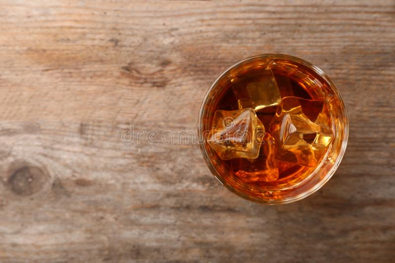 Golden whiskey in glass with ice cubes on wooden table, top view. royalty free stock image