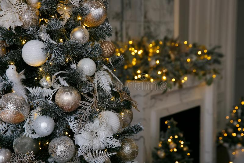 Golden and white Christmas decorations on the New Year tree in the home interior. On the eve of the holiday royalty free stock photo