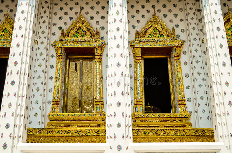Golden window of Thai temple with white marble wall royalty free stock images