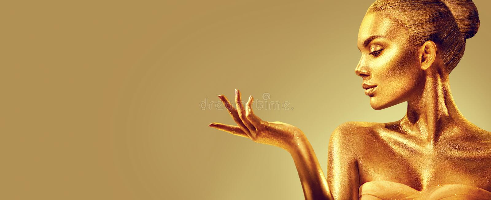 Golden woman. Beauty fashion model girl with golden skin, makeup, hair and jewellery on gold background. Fashion art portrait stock images