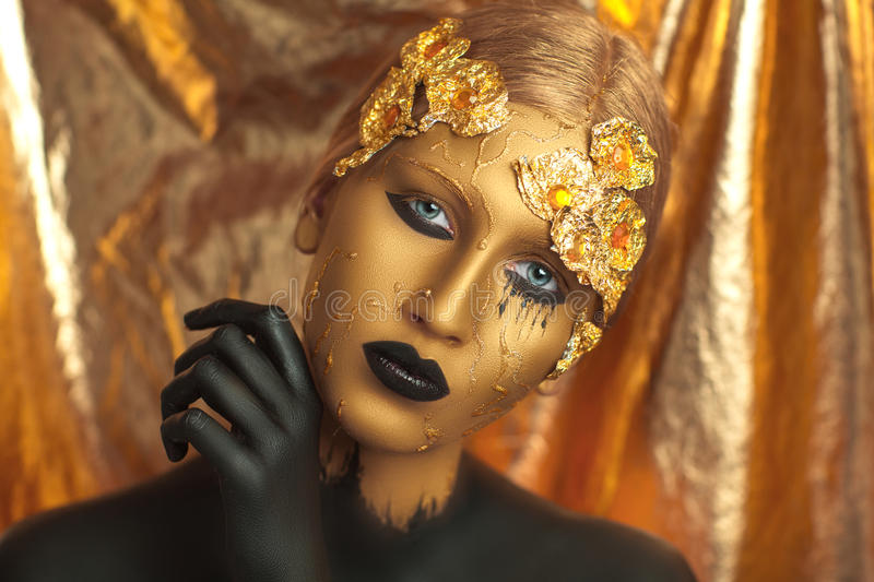 Golden woman. Magic golden girl with bright makeup. Streams of gold, shiny tears drops on the cheeks, black hand in the paint for body art. Big lips, long royalty free stock photography