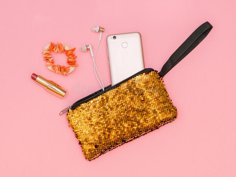 Golden women`s handbag with phone and lipstick and bracelet on a pink table. Pastel color. Flat lay. Golden women`s handbag with phone and lipstick on a pink stock image