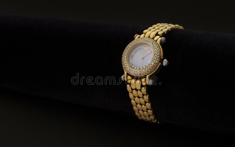 Golden women wrist watch with precious stones on dark background royalty free stock photography