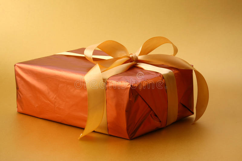 Golden wrapped gift. With satin ribbon bow on golden background stock photos
