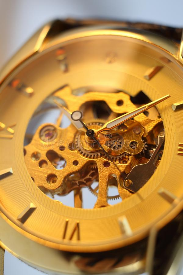 Golden wrist mechanical watch close-up on a white background. Clock face. Time. royalty free stock image