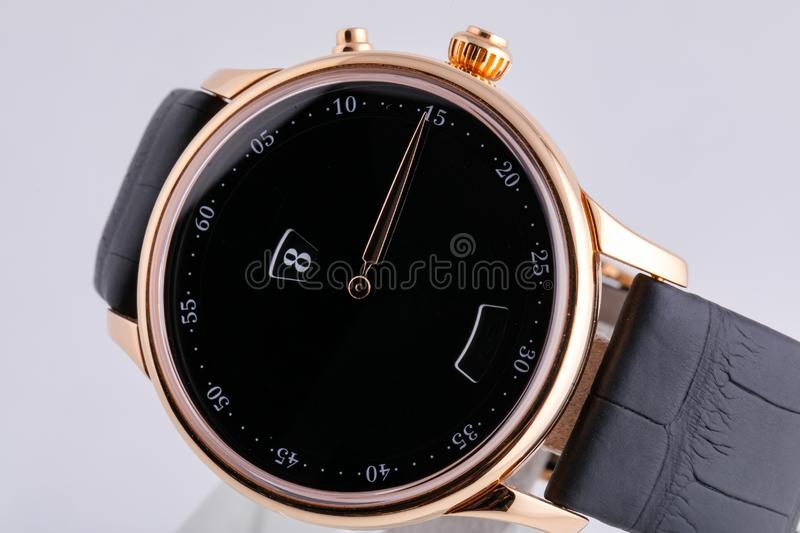 Golden wristwatch with black dial, black clockwise, chronograph on black leather strap  on white background stock image