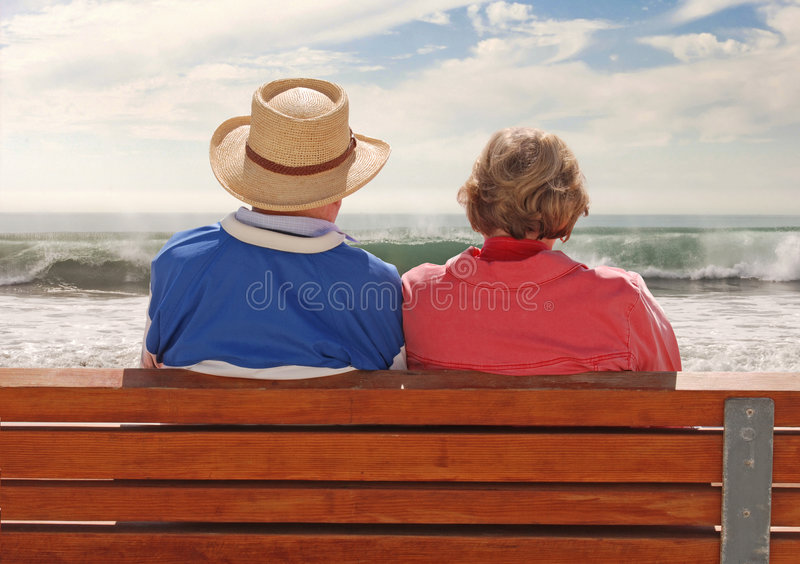Golden Years. A senoir adult couple sitting at a benchand, enjoying their time at the beach royalty free stock photos