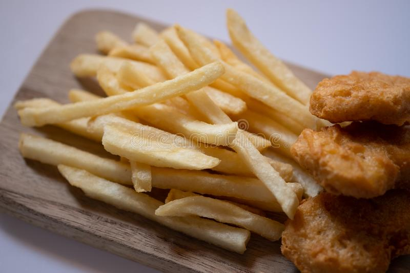 Golden yellow french fries and chicken nuggets on wooden plate. Closed up stock image