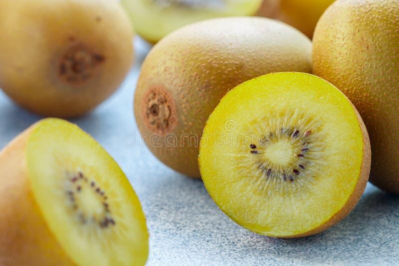 Golden yellow organic kiwi. Whole and cut ripe juicy fruits on grey background. kiwifruit royalty free stock photo
