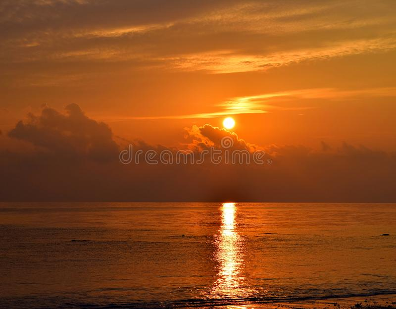 Golden Yellow Shining Sun Rising at Horizon with Reflection in Sea Water with Warm Colors in Clouds in Morning Sky royalty free stock photo