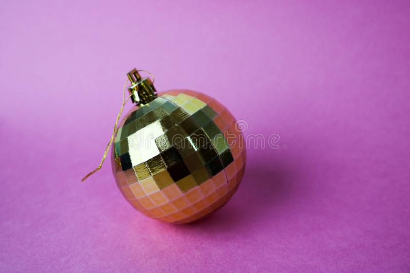 Golden yellow small round glass plastic winter smart shiny decorative beautiful xmas festive Christmas ball, Christmas toy. Pasted over with spangles on a stock photo
