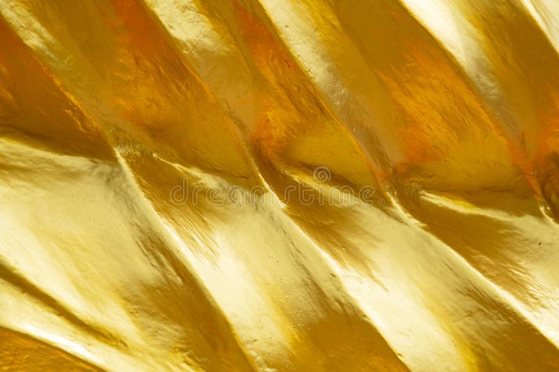 Golden Yellow Texture Background. Close-up of gold leaf gilt detail on a buddha statue in Wat Phra Yai located on Pranak Hill in Pattaya, Chonburi, Thailand stock photos