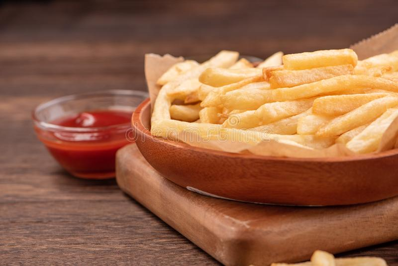 Golden yummy deep French fries on kraft baking sheet paper and serving tray to eat with ketchup and yellow mustard, close up, royalty free stock photography
