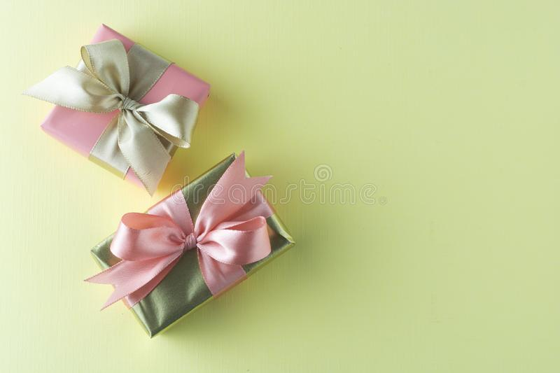 Goldenand pink gift isolated on yellow background. Birthday, Christmas party mock up. Copy space stock photos