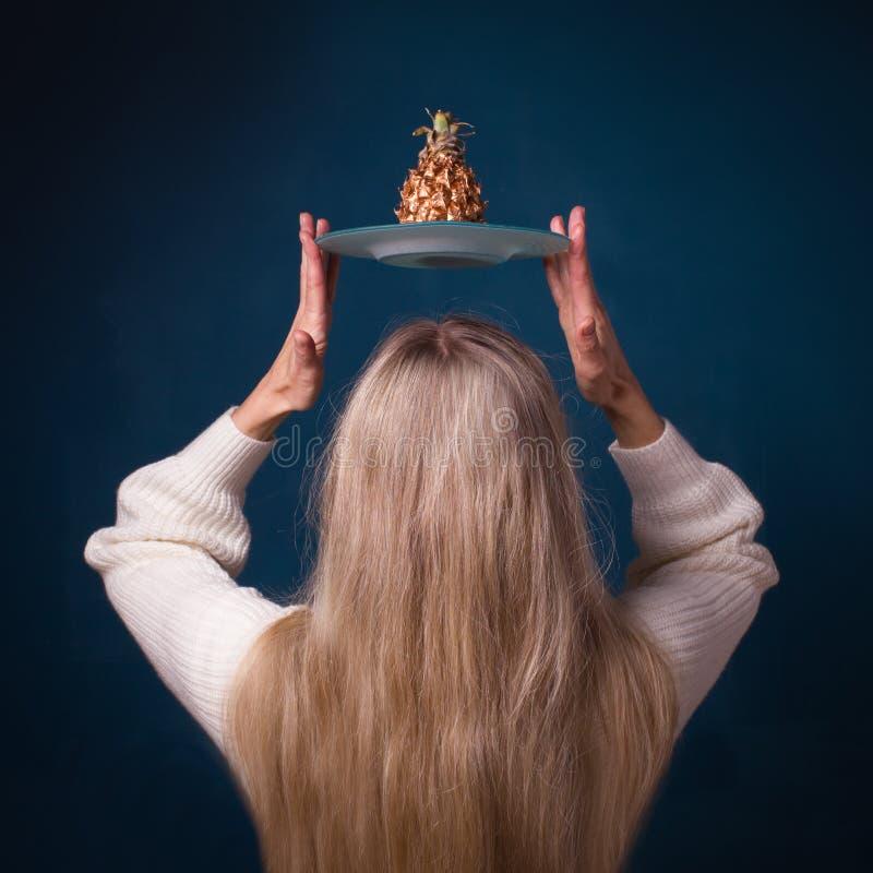 Goldene Ananasfrucht über dem Kopf der Frau stockfoto
