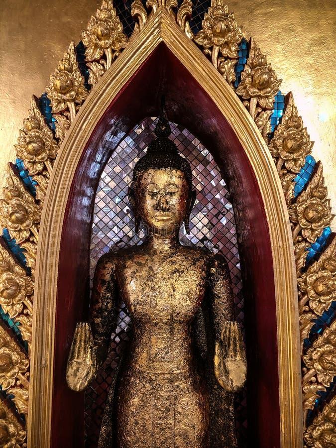 Goldene antike Stellungsbuddha-Statue im thailändischen Tempel stockfotografie