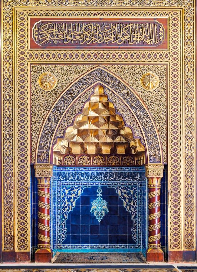Goldene aufwändige gewölbte Mihrabnische mit Blumenmuster, blauen türkischen Keramikfliesen und arabischer Kalligraphie, Kairo, Ä stockfotos