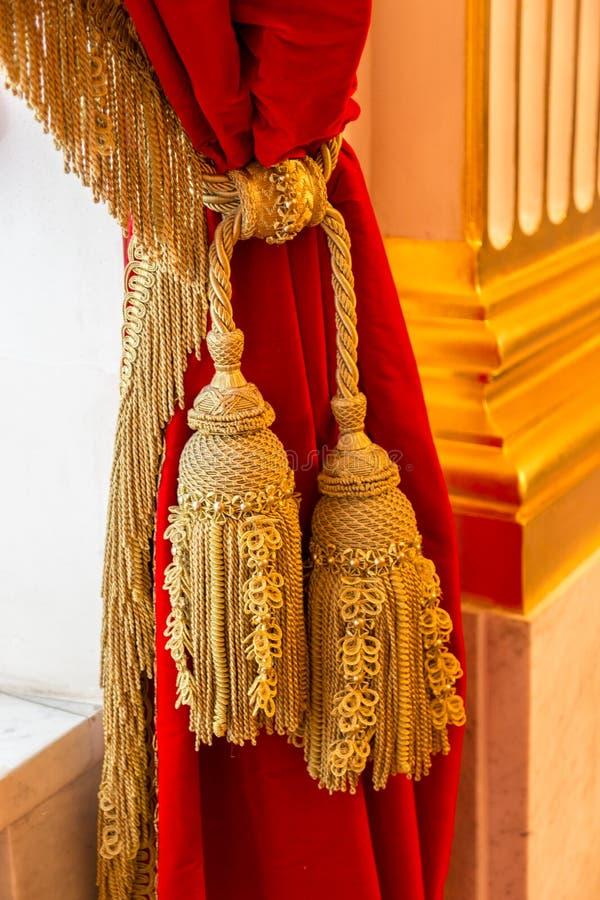 Goldene Bürste auf einem roten Samtvorhang stockbilder