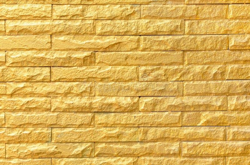 Goldene Backsteinmauerhintergrund-Musterbeschaffenheit lizenzfreies stockfoto