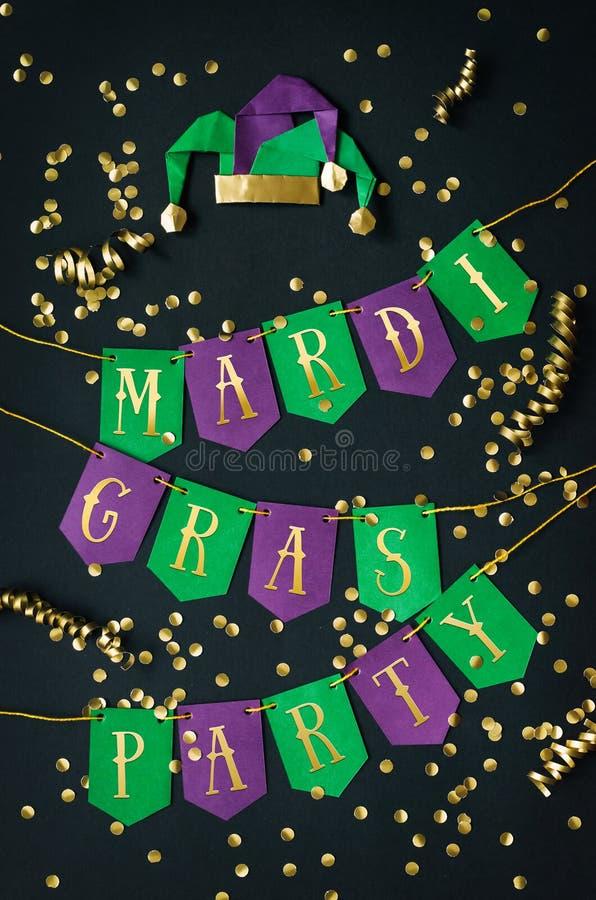 Goldene Beschriftung des Faschingsballs auf handgemachtem Papiergrün und purpurroter festlicher Girlande, schwarzer Hintergrund,  lizenzfreies stockfoto