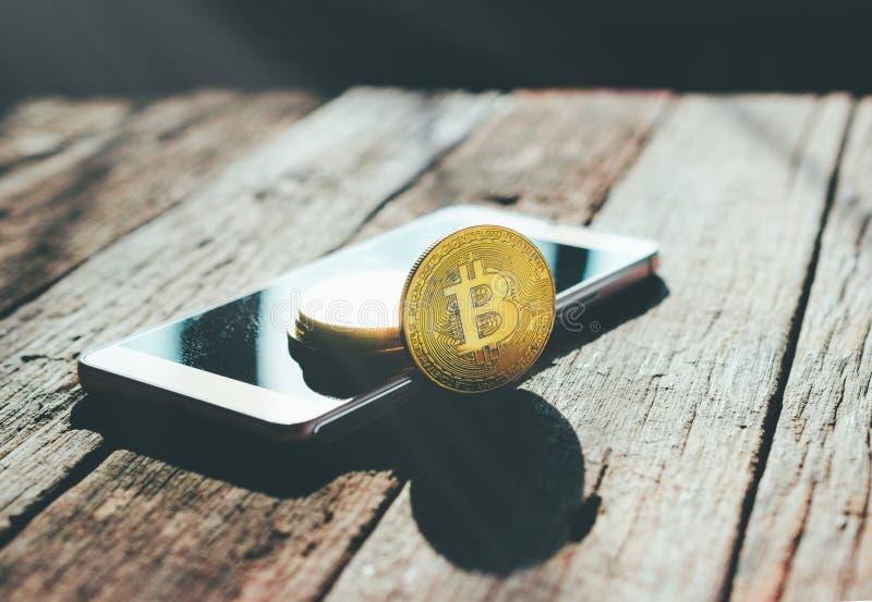 goldene bitcoin Münze auf Handy Schlüsselwährungshintergrund c lizenzfreies stockbild
