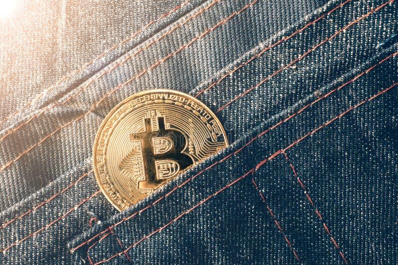 Goldene bitcoin Münze in der Jeanstasche lizenzfreie stockfotos