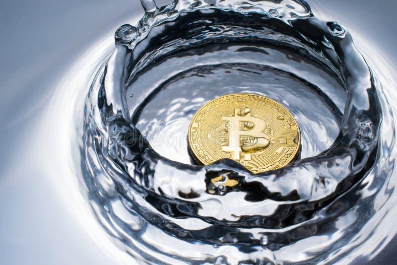 goldene bitcoin Münze mit Wasserspritzenschlüsselwährungshintergrund lizenzfreies stockbild