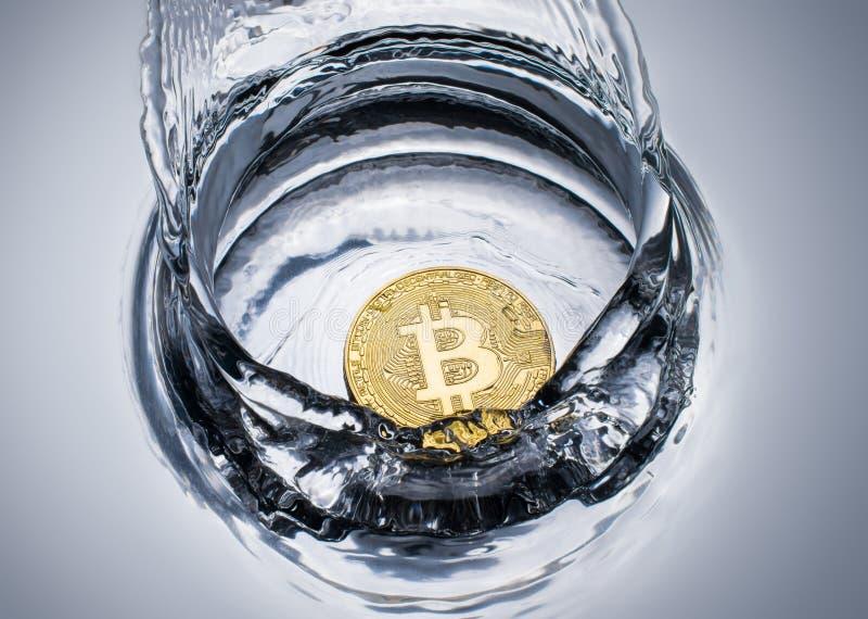 goldene bitcoin Münze mit Wasserspritzenschlüsselwährungshintergrund lizenzfreie stockfotos