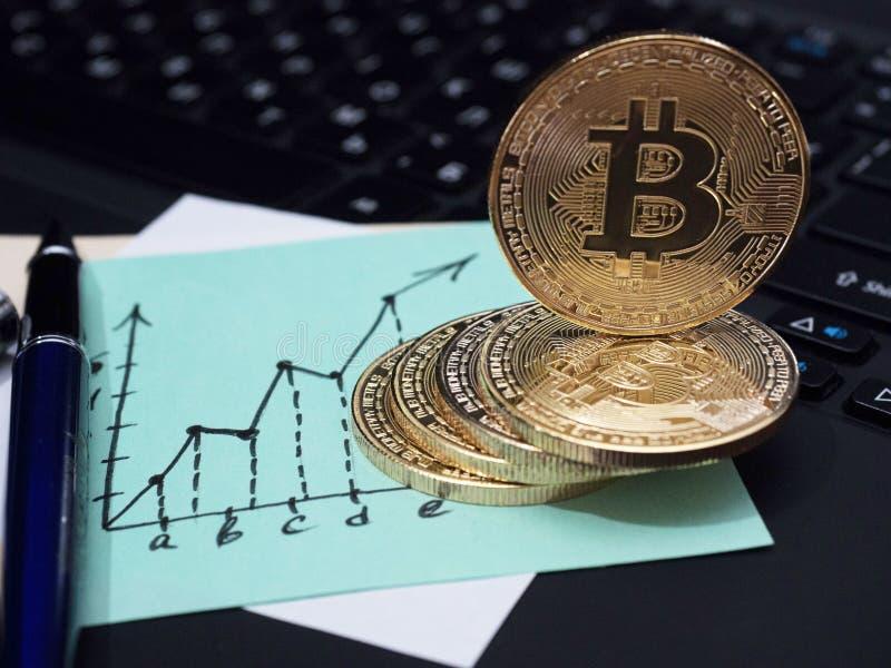 Goldene Bitcoin-Münzen auf der Laptoptastatur Geschäftsanmerkung in Form eines Diagramms stockbilder