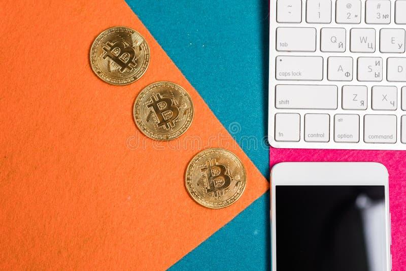 Goldene bitcoins auf eine Oberseite und intelligentes Telefon und Laptop lizenzfreies stockfoto