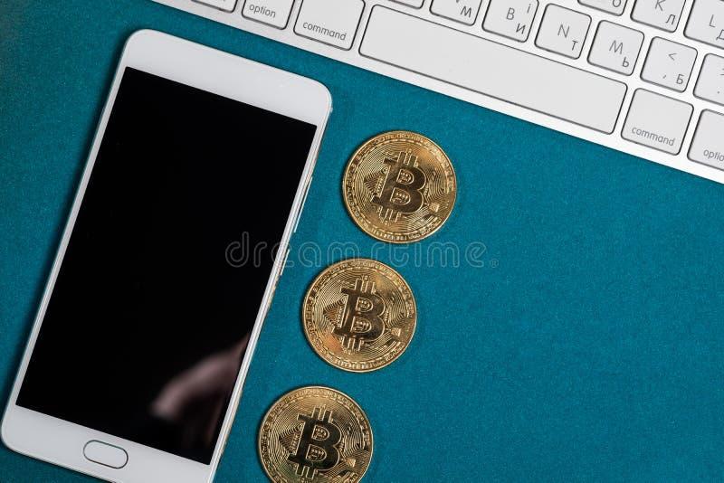 Goldene bitcoins auf eine Oberseite und intelligentes Telefon und Laptop stockbild