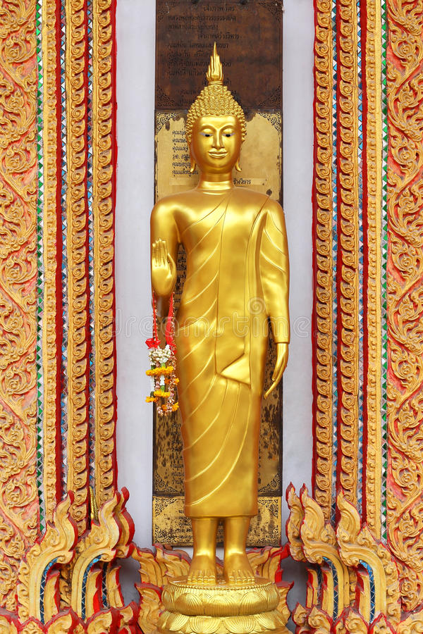 Goldene Buddha-Statue, die mit Girlande steht lizenzfreie stockfotos