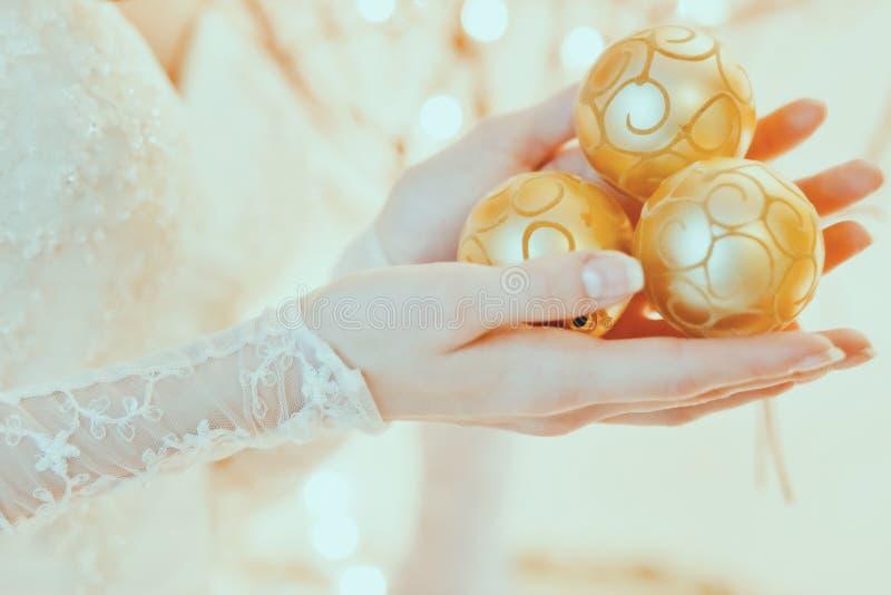 Goldene Dekorationen Christnas in den Brauthänden lizenzfreie stockbilder