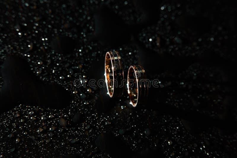 Goldene Eheringe auf Dunkelheit lizenzfreies stockfoto
