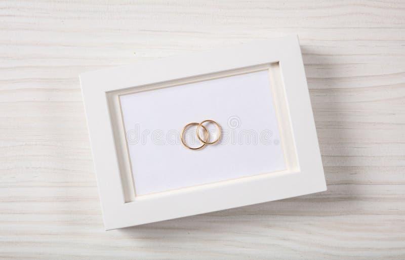 Goldene Eheringe auf einem leeren weißen Fotorahmen, Draufsicht, über einen weißen hölzernen Hintergrund stockbilder