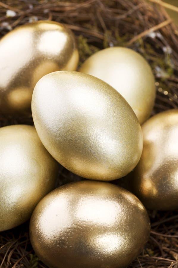 Goldene Eier in einem Nest stockbilder