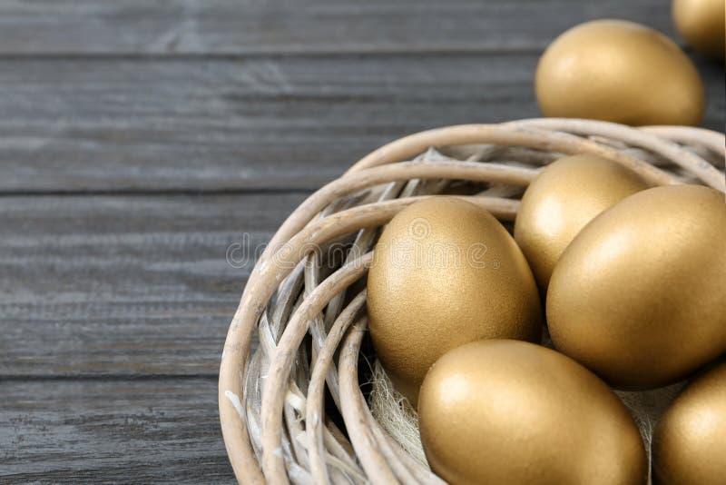 Goldene Eier im Nest auf hölzernem Hintergrund stockbilder