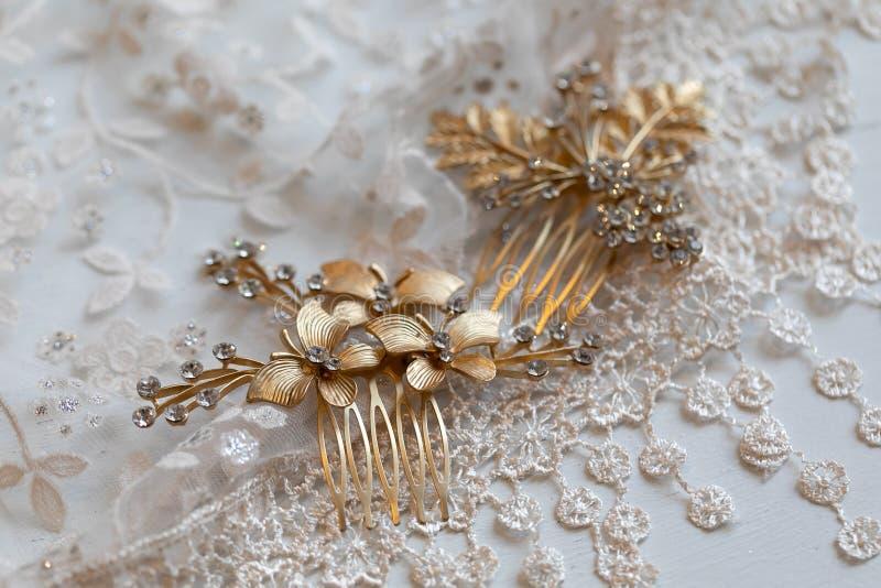 Goldene Farbe der weiblichen Haarspange mit Blumen, Blätter, die auf dem Tulle-Material mit Mustern in Form der Blumen liegen lizenzfreie stockfotografie