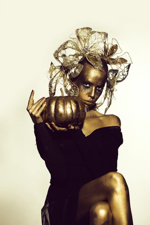 goldene Frau mit Halloween-Kürbis lizenzfreie stockbilder