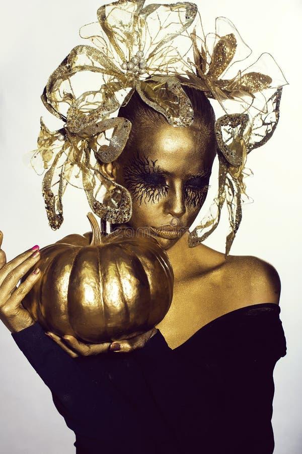 goldene Frau mit Halloween-Kürbis stockfotografie